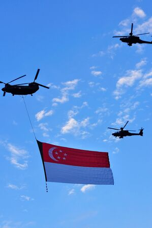 during the day: Chinook flying the Singapore state flag during National Day Parade Combined Rehearsal June 19, 2010 in Singapore