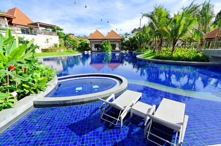 Tropical resort with swimming pool and deck chair for relaxation
