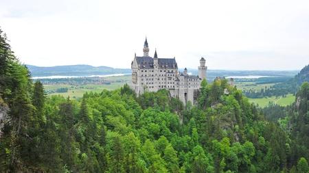 Famous Neuschwanstein Castle overlooking the surrounding valley and meadow, in Schwangau, Germany