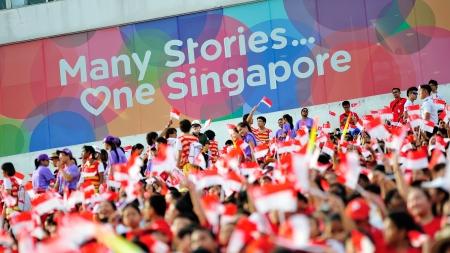 spectators: SINGAPUR - 20 de julio espectadores agitaban banderas de Singapur durante el desfile del D�a Nacional de NDP Rehearsal 2013 el 20 de julio de 2013 en Singapur Editorial