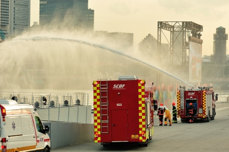 compressed air: SINGAPORE - JULY 20  Singapore Civil Defense Force  SCDF  compressed air foam engine spraying water jets during National Day Parade  NDP  Rehearsal 2013 on July 20, 2013 in Singapore