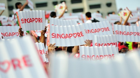 SINGAPORE - JULY 20: Spectators waving Singapore banners during National Day Parade (NDP) Rehearsal 2013 on July 20, 2013 in Singapore