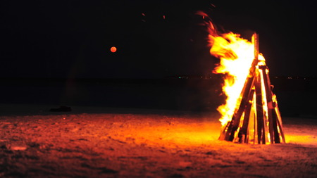 Bonfire burning on a private island as the blood moon rise above the Laccadive Sea in Maldives
