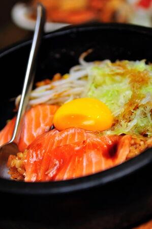Korean salmon bibimbap in hot stone bowl photo