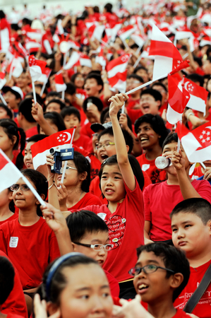 grand kid: SINGAPORE - JULY 11: Primary school students waving Singapore flags during National Day Parade Combine Rehearsal July 11, 2009 in Singapore