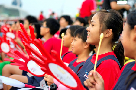 during the day: SINGAPORE - JULY 11: Primary school students participating with drum kit during National Day Parade Combine Rehearsal July 11, 2009 in Singapore