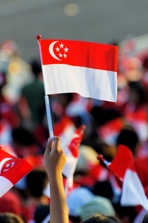 Audience waving Singapore flag during Singapore National Day Parade (NDP) Rehearsal at Singapore Marina Bay Floating Platform on 25 Jul 2009. Editorial