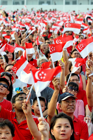 SINGAPORE - AUGUST 09: Audience waving flags during Singapore National Day Parade 2009 August 09, 2009 in Singapore