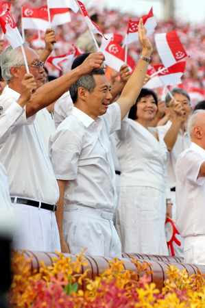 ministers: SINGAPORE - AUGUST 09: Ministers waving flags during Singapore National Day Parade 2009 August 09, 2009 in Singapore