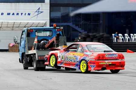 towed: SINGAPORE - JULY 05: Red coupe being towed away during Formula Drift Singapore 2009 Pro-am Series July 05, 2009 in Singapore.