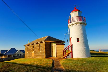 navigation aid: Historic lighthouse and cottage on hill top Stock Photo