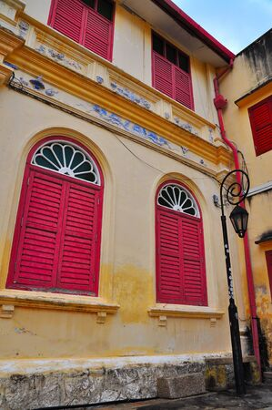 louvered: Historic building exterior with red louvered windows Stock Photo
