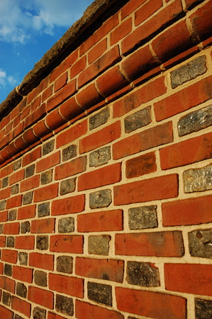 embed: Red brick wall against blue sky