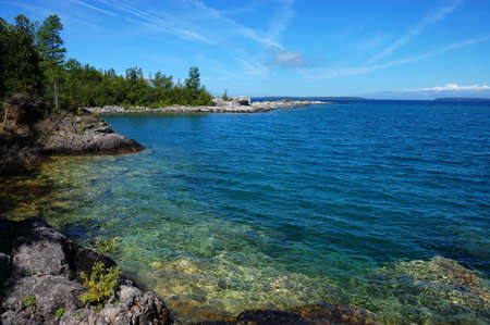 colorfu: Rocky shore and clear lake water at Georgian Bay with blue sky Stock Photo