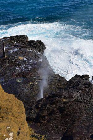 blowhole: Halona Blowhole spraying water through its lava tube in Oahu, Hawaii Stock Photo