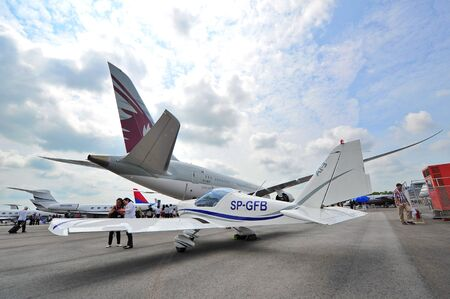 turboprop: SINGAPORE - FEBRUARY 12: Aero AT-3 R100 turboprop aircraft on display behind the Qatar Airways Boeing 787-8 Dreamliner at Singapore Airshow February 12, 2014 in Singapore