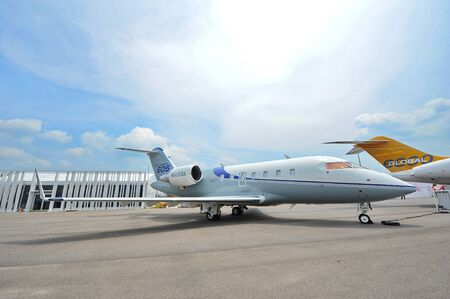 twin engine: SINGAPORE - FEBRUARY 9: Bombardier Challenger 605 twin engine executive jet on display at Singapore Airshow February 9, 2014 in Singapore