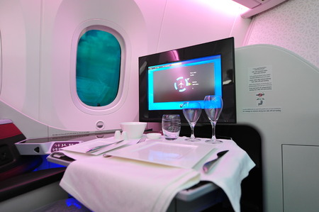 12 class: SINGAPORE - FEBRUARY 12: Comfortable business class seat with dining setting onboard Qatar Airways Boeing 787-8 Dreamliner at Singapore Airshow February 12, 2014 in Singapore