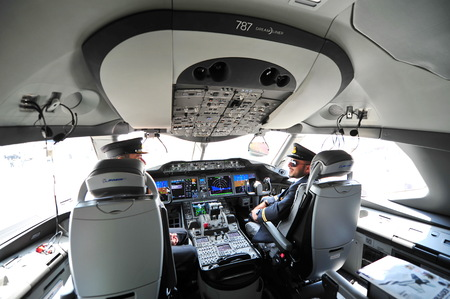 SINGAPORE - FEBRUARY 12: Pilots in the cockpit of Qatar Airways Boeing 787-8 Dreamliner at Singapore Airshow February 12, 2014 in Singapore Editorial