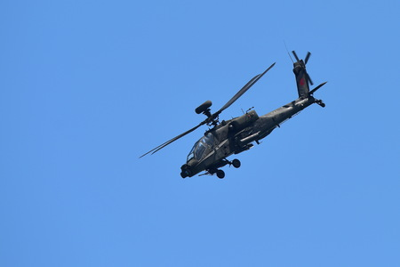aerobatics: SINGAPORE - FEBRUARY 16:  RSAF AH-64D Apache helicopter performing aerobatics at Singapore Airshow February 16, 2016 in Singapore
