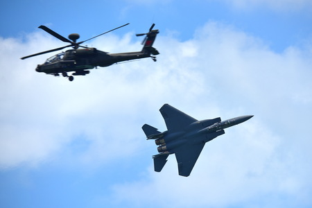 apache: SINGAPORE - FEBRUARY 16: RSAF F-15SG fighter jet and Apache helicopter performing aerobatics at Singapore Airshow February 16, 2016 in Singapore