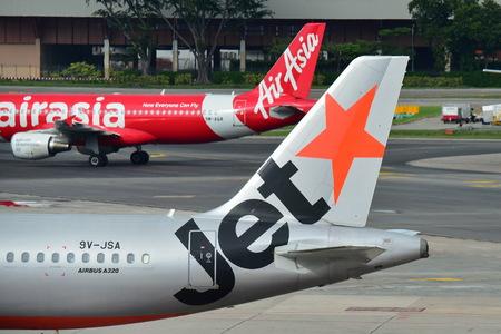 シンガポール - 12 月 23 日: ライバル エアアジアと 2016 年 12 月 23 日にシンガポールのチャンギ空港でジェット スター アジア A320 報道画像