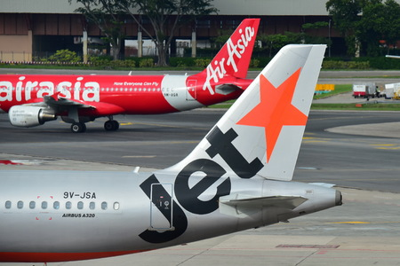 SINGAPORE - DECEMBER 23: Rivals Air Asia and Jetstar Asia Airbus A320 at Changi Airport on December 23, 2016 in Singapore Редакционное