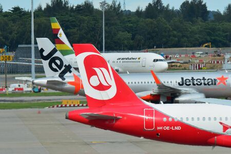 SINGAPORE - DECEMBER 23: Tails of Air Zimbabwe Boeing 767, Jetstar Asia Airbus A320 and Air Belin Airbus A320 at Changi Airport on December 23, 2016 in Singapore