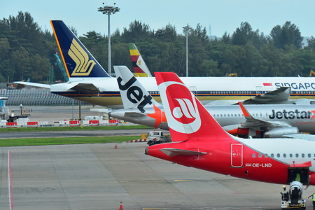 SINGAPORE - DECEMBER 23: Tails of Singapore Airlines, Air Zimbabwe, Jetstar Asia and Air Berlin aircraft at Changi Airport on December 23, 2016 in Singapore