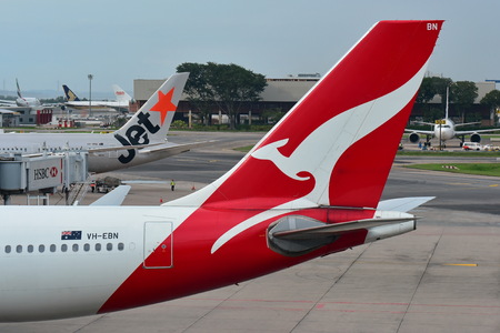 SINGAPORE - DECEMBER 23: Tails of Jetstar International and Qantas aircraft belonging to the same family at Changi Airport on December 23, 2016 in Singapore Editorial