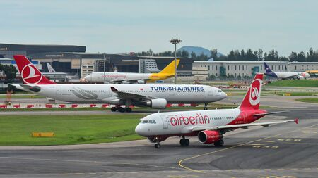 SINGAPORE - DECEMBER 23: Air Berlin A320 and Turkish Airlines A330 taxiing at Changi Airport on December 23, 2016 in Singapore Editorial
