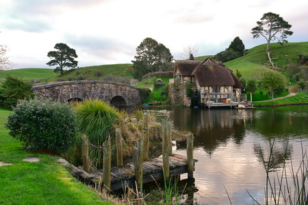 MATAMATA, NEW ZEALAND - AUGUST 2017: Bridge and water mill in Hobbiton movie set featured in Lord of the Rings and Hobbit movies on August 27, 2017 in Matamata