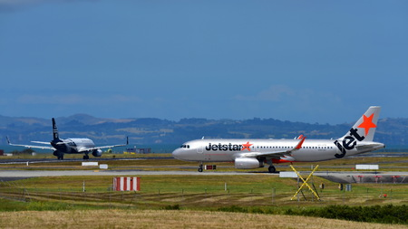 AUCKLAND, NEW ZEALAND - DECEMBER 17: Jetstar and rival Air New Zealand Airbus A320s taxiing at Auckland International Airport on December 17, 2017 in Auckland