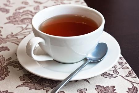 afternoon cafe: El blanco de la taza con el t� negro en madera oscura Foto de archivo