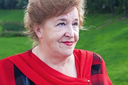 Closeup portrait of smiling elegant senior lady in red Stock Photo - 10445587