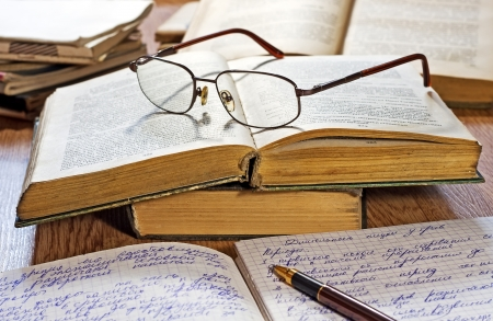 Opened notebook, pen, books and glasses on the wooden table  photo