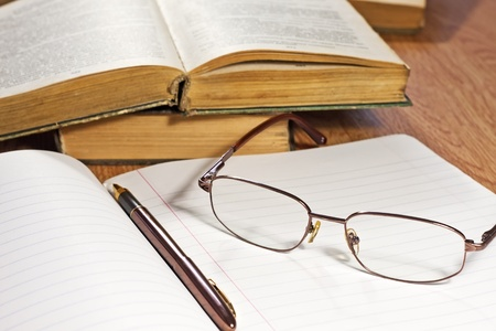 Open notebook with pen and glasses on wooden table Stock Photo - 10606971
