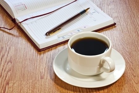 Coffee cup, pen, opened organizer, standing on the wooden table photo