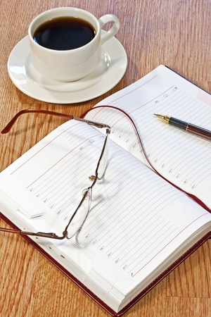 everyday jobs: workplace at morning: coffee, notebook, pens, glasses on the table