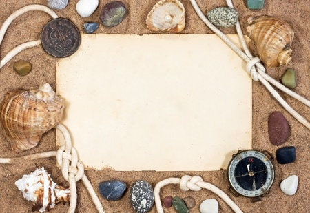 Old paper, sea shells and rope on sand background  photo