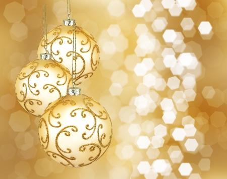 Tres hermosas bolas de navidad de oro sobre un fondo dorado