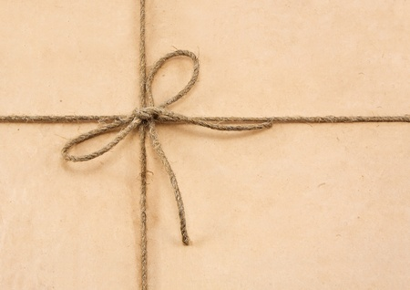 pack string: String tied in a bow on a brown recycled paper