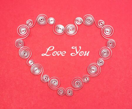 Handmade heart cut from white paper on red background. Quilling. photo