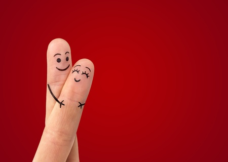 two fingers: A happy couple in love with painted smiley and hugging