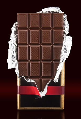 chocolate bar with open cover on dark background photo