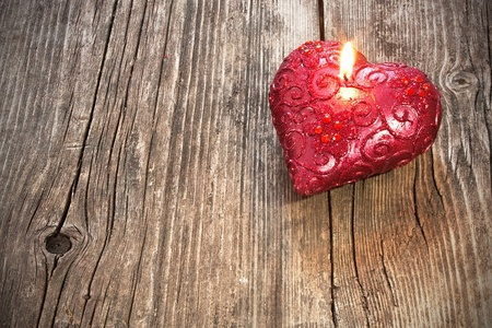 Red heart shaped candle on wooden background photo