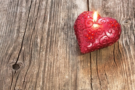 burning love: Red heart shaped candle on wooden background Stock Photo