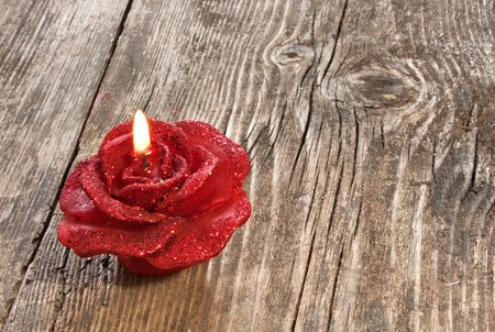 wedding night: Red rose shaped candle on wooden background