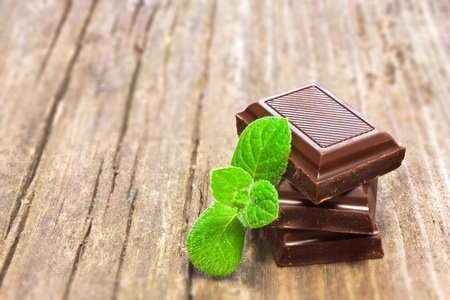 chocolate mint: Dark chocolate with fresh mint leaves on wooden background