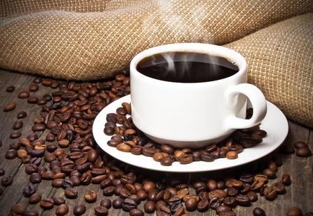 Taza de caf� en grano de caf� en la mesa de madera vieja